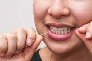 Closeup photo of a young woman who is using dental floss to keep her teeth and gums healthy as recommended by Cosmetic Dentistry of Murfreesboro - a dentist office in Murfreesboro, TN.