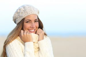 A caucasian woman with long, brownish-blonde hair and brown eyes. She is dressed in a white, knit sweater and is also wearing a white, knit beret-style hat on her head and an off-white scarf around her neck. She is clutching at the scarf as if she is cold. She is smiling and has nice, straight, white teeth and healthy gums. Probably a patient of Cosmetic Dentistry of Murfreesboro- a dentist office in Murfreesboro, TN.
