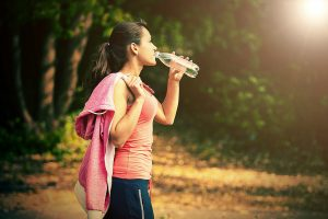 Photo of a young, slender caucasian woman with dark, brown hair. She is wearing sports attire and she is outside in nature and drinking from a plastic bottle of water.