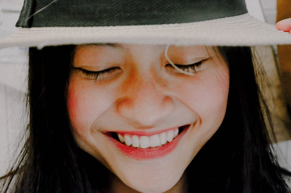 Young woman with a pretty smile wearing a hat.