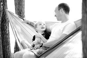 man with dental bridge smiling at son while sitting in hammock
